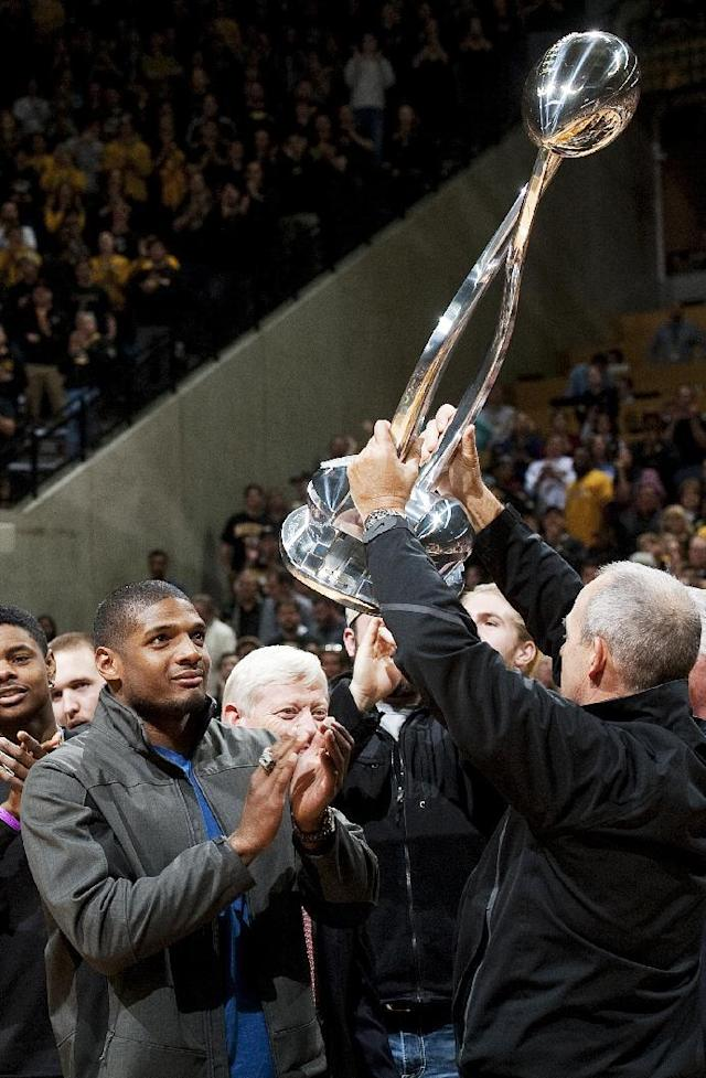 Missouri's All-American defensive end Michael Sam, left, watches head coach Gary Pinkel, right, raise the Cotton Bowl trophy during a presentation at halftime of an NCAA college basketball game between Missouri and Tennessee, Saturday, Feb. 15, 2014, in Columbia, Mo. Sam came out to the entire country Sunday, Feb. 9, and could become the first openly gay player in the NFL. (AP Photo/L.G. Patterson)