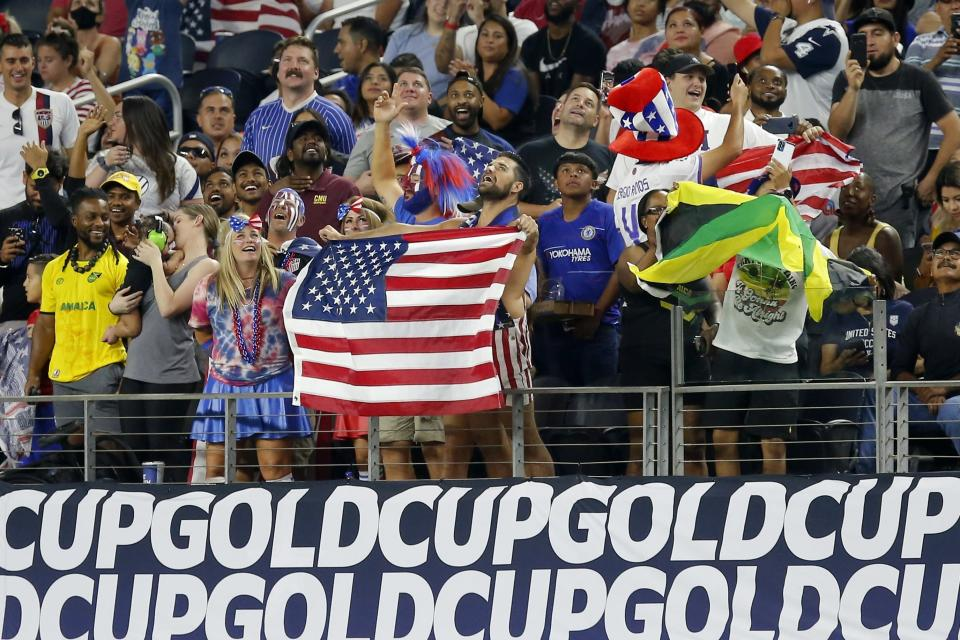 Fans wave American and Jamaican flags during team warmups before a 2021 CONCACAF Gold Cup quarterfinals soccer match, Sunday, July 25, 2021, in Arlington, Texas. (AP Photo/Brandon Wade)