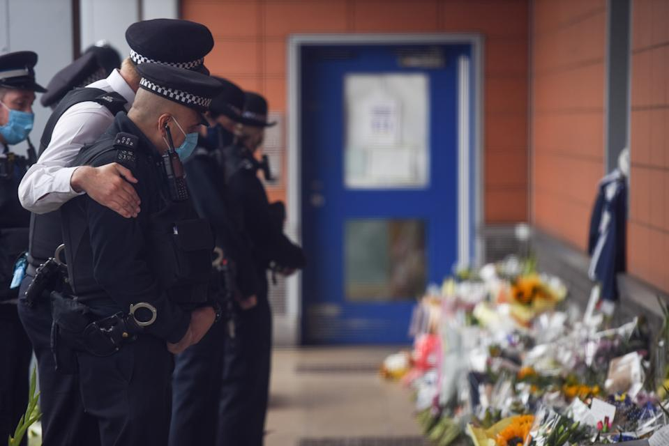 CROYDON, ENGLAND - SEPTEMBER 27: A Police officer comforts a colleague while paying tribute to Sergeant Matiu Ratana outside Croydon Custody Centre on September 27, 2020 in Croydon, England. Metropolitan Police Custody sergeant Matiu Ratana, 54, was shot dead in the early hours of Friday 25 September At Croydon Custody Suite. A handcuffed man being checked in by Sgt Ratana opened fire before turning the weapon on himself. Sgt Ratana died later in hospital. (Photo by Peter Summers/Getty Images)