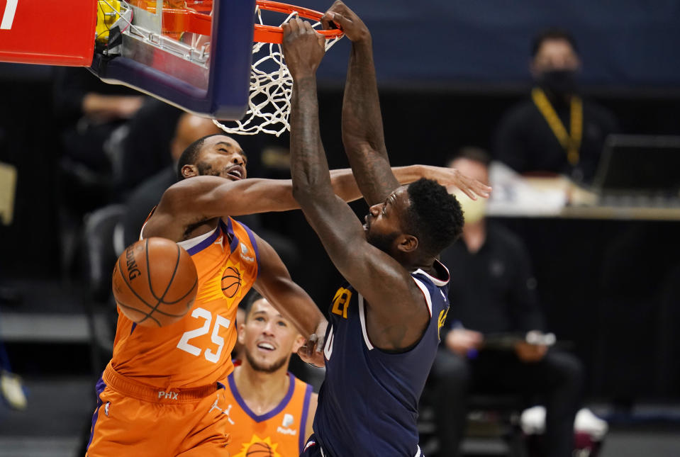 Phoenix Suns forward Mikal Bridges, left, fouls Denver Nuggets forward JaMychal Green on a dunk during the second half of an NBA basketball game Friday, Jan. 1, 2021, in Denver. (AP Photo/David Zalubowski)