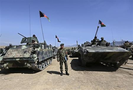 An Afghan National Army officer stands among tanks before a military exercise on the outskirts of Kabul