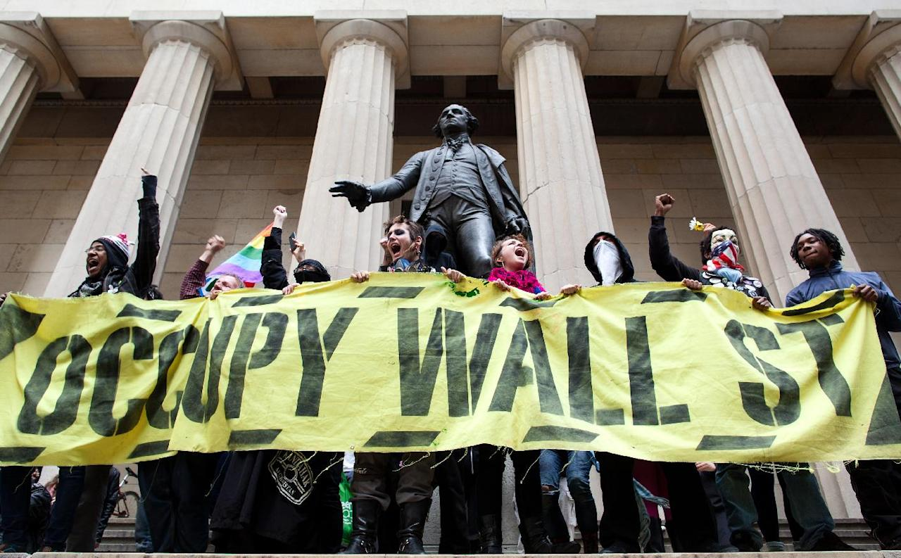 Occupy Wall Street demonstrators stand and cheer in front of the George Washington statue on Wall Street as they celebrate the protest's sixth month, Saturday, March 17, 2012, in New York. With the city's attention focused on the huge St. Patrick's Day Parade many blocks uptown, the Occupy rally at Zuccotti Park on Saturday drew a far smaller crowd than the demonstrations seen in the city when the movement was at its peak in the fall. A couple hundred people attended. (AP Photo/John Minchillo)