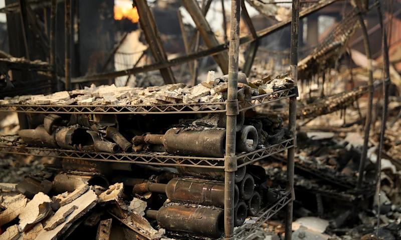 Burned out wine bottles sit on a rack at the fire damaged Signarello Estate winery.