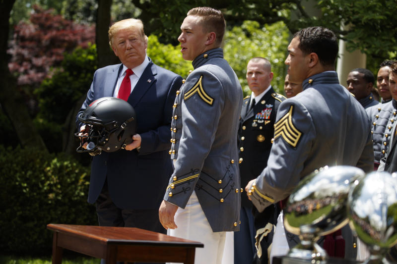 President Donald Trump looks on as Army linebacker Cole Christiansen speaks.