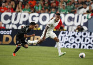 Mexico defender Jorge Sanchez, left, pursues Canada defender Mark-Anthony Kaye during the first half of a CONCACAF Gold Cup soccer match Wednesday, June 19, 2019, at Mile High Stadium in Denver. (AP Photo/David Zalubowski)