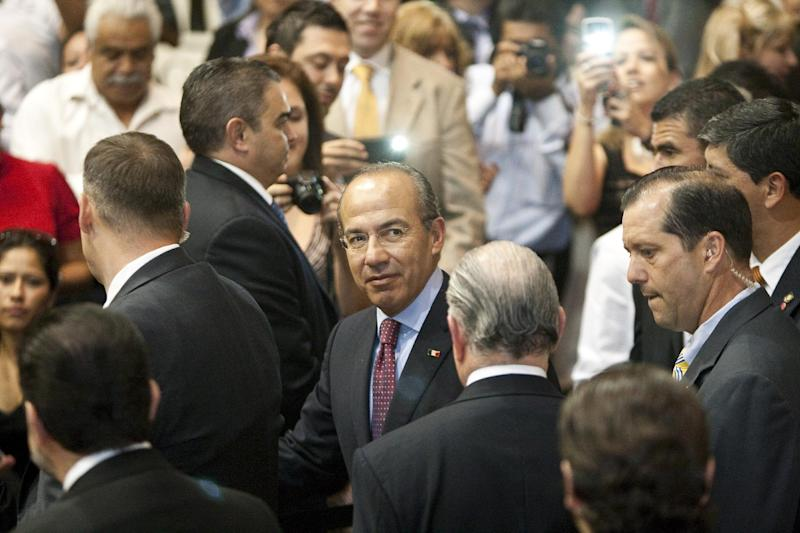 Mexican President Felipe Calderon shakes hands as he walks to his seat at the Ripley House community center gymnasium in Houston, Wednesday, April 25, 2012. Calderon spoke to more than 200 Mexican immigrants at the community center in Houston. The speech was part of a daylong visit by Calderon, who also met with local business leaders and Houston's mayor. (AP Photo/Houston Chronicle, Nick de la Torre)