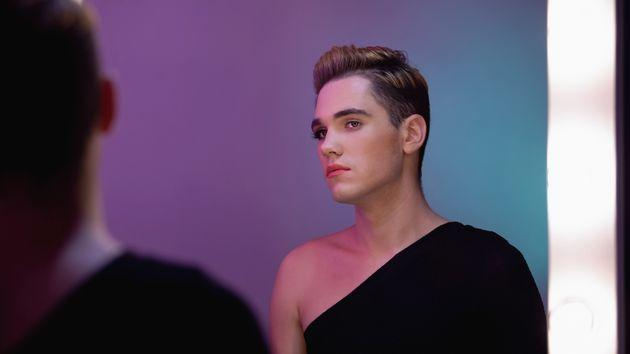 Genderqueer with half-face makeup looking in mirror, non-binary identity concept (Photo: Motortion via Getty Images/iStockphoto)
