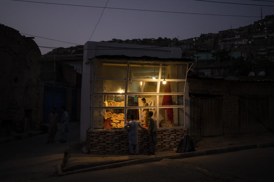 Customers wait outside a small bakery at dusk in Kabul, Afghanistan, Friday, Sept. 10, 2021. (AP Photo/Bernat Armangue)