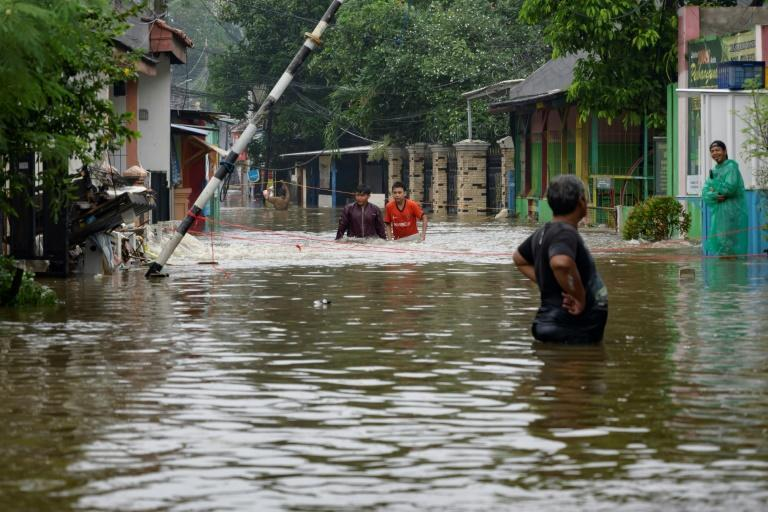 Residents wade through a flooded road in Jakarta on Saturday following heavy rains overnight