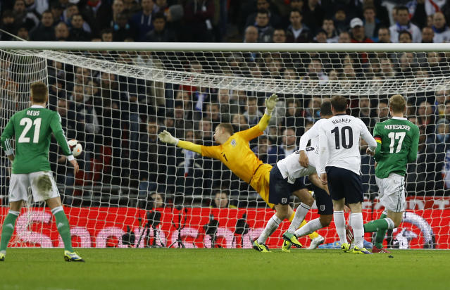 Germany's Per Mertesacker, right, watches his ball goes pass England's goalkeeper Joe Hart into the net during the international friendly soccer match between England and Germany, at Wembley Stadium in London, Tuesday, Nov. 19, 2013. (AP Photo/Kirsty Wigglesworth)
