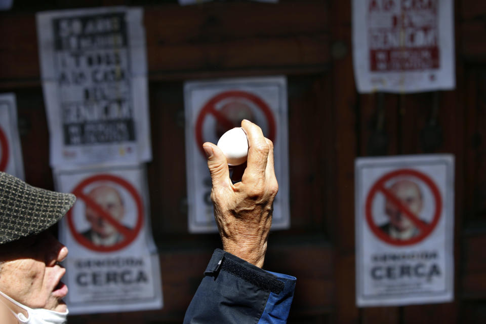 """David Roura, a member of the 1968-71 student movement, prepares to throw an egg at the front gate residence of former Mexican President Luis Echeverría, (1970-1976), during a march to commemorate the 50th anniversary of the student massacre of 1971 known as """"El Halconazo,"""" in Mexico City, Thursday, June 10, 2021. The attack, also known as the Corpus Christi massacre, was carried out by a group of men apparently recruited by the government to dissolve a pro-democracy student demonstration. (AP Photo/Marco Ugarte)"""