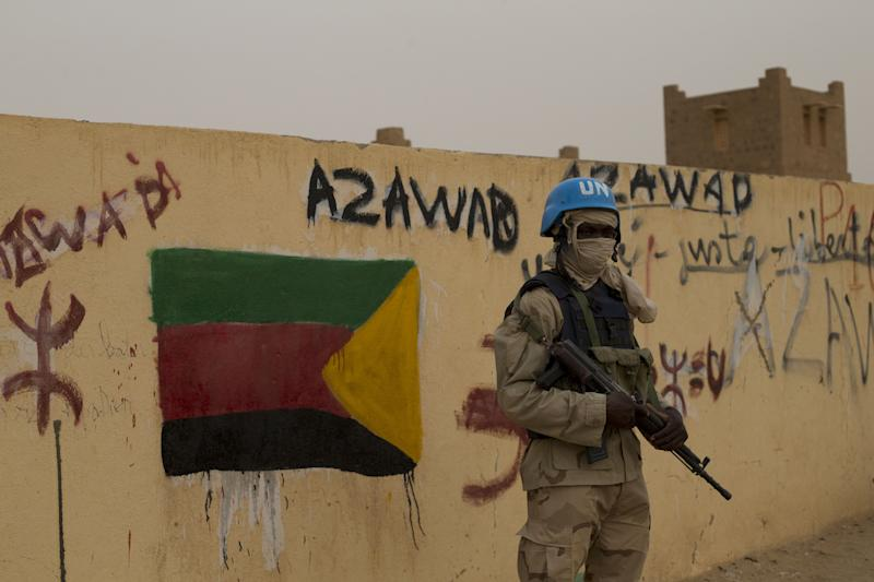 FILE - In this Sunday, July, 28, 2013 file photo, a United Nations peacekeeper stands guard at the entrance to the main polling station, covered in separatist flags and graffiti supporting the creation of the independent state of Azawad, in Kidal, Mali. Mali's new president-elect Ibrahim Boubacar Keita, whose rival conceded defeat Monday, Aug. 12, a day after the vote, now faces the challenge of finding a resolution to the simmering separatist rebellion in the country's north. Based on his recent campaign visit to the rebel's stronghold, during which the NMLA tried to block his plane from landing, and then hurled stones at it while parked, the path to reconciliation is not likely to be easy.(AP Photo/Rebecca Blackwell, File)