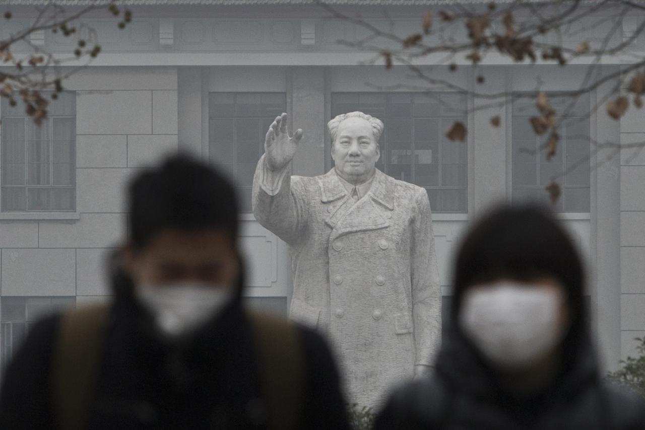 People wearing masks walk in front of the statue of late Chinese leader Mao Zedong in a university, during a hazy day in downtown Shanghai December 26, 2013. China is struggling to meet its 2011-2015 targets to reduce pollution, cut greenhouse gas growth and introduce cleaner sources of energy, a report submitted to the country's parliament said on Wednesday. REUTERS/Aly Song (CHINA - Tags: POLITICS ENERGY ENVIRONMENT SOCIETY EDUCATION TPX IMAGES OF THE DAY)