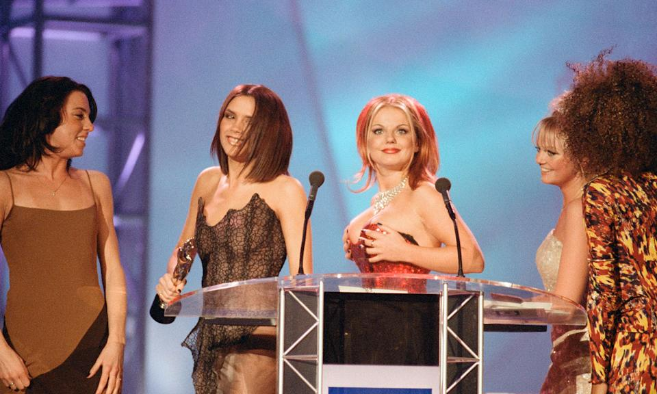 "Ginger Spice gave everyone at the Brits (and everyone watching at home) a huge eyeful in 1997. The bustier part of Geri's red dress slipped down as she and her bandmates stepped up to the podium as she accidentally exposed her right breast. It was a night of daring sartorial choices from the redhead as it was also the year she ensured her place in pop history with <a href=""https://www.harpersbazaar.com/uk/fashion/fashion-news/news/a40047/story-of-geri-halliwell-union-jack-brits-dress/"" rel=""nofollow noopener"" target=""_blank"" data-ylk=""slk:the iconic Union Jack tea towel dress"" class=""link rapid-noclick-resp"">the iconic Union Jack tea towel dress</a>. (John Ferguson/Mirrorpix/Getty Images)"