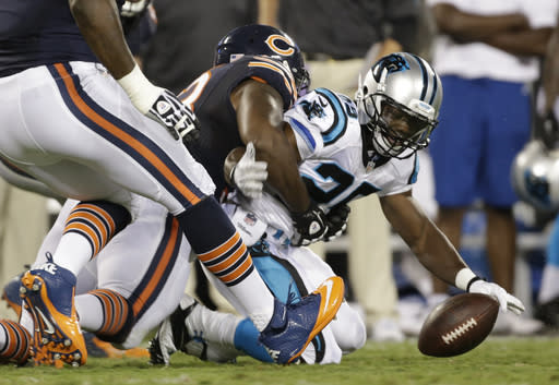 Carolina Panthers' Kenjon Barner, right, fumbles the ball after being hit by Chicago Bears' Nate Collins, left, during the first half of a preseason NFL football game in Charlotte, N.C., Friday, Aug. 9, 2013. The Bears recovered the ball. (AP Photo/Bob Leverone)