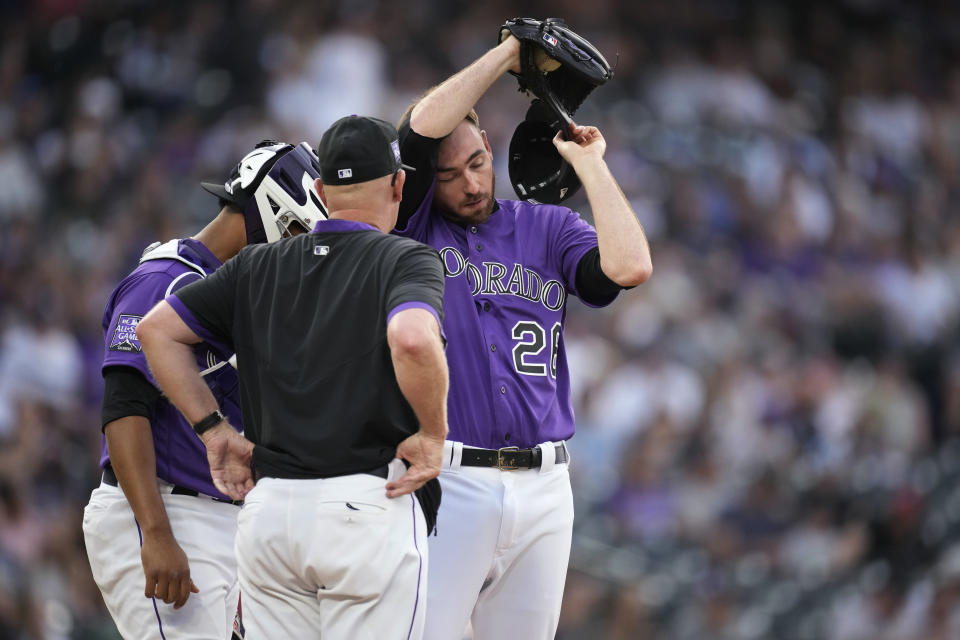 Colorado Rockies pitching coach Steve Foster, front, confers with catcher Elias Diaz, left, and starting pitcher Austin Gomber during the first inning of the team's baseball game against the Milwaukee Brewers on Saturday, June 19, 2021, in Denver. (AP Photo/David Zalubowski)