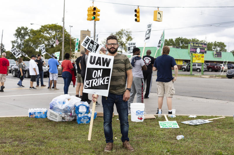 In this Monday, Sept. 16, 2019, photo Joe Drumm, who has been with General Motors for 12 years, stands outside of GM plants with other union members picketing in Flint, Mich. More than 49,000 members of the United Auto Workers went on strike Monday against General Motors, bringing more than 50 factories and parts warehouses to a standstill in the union's first walkout against the No. 1 U.S. automaker in over a decade. (Sara Faraj/The Flint Journal via AP)