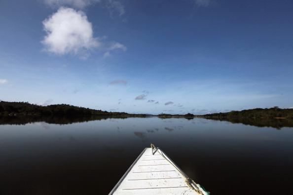 A boat navigates the Xingu River near the site where the Belo Monte dam complex is under construction in the Amazon basin on June 14, 2012 near Altamira, Brazil. Belo Monte will be the world's third-largest hydroelectric project and will displace up to 20,000 people while diverting the Xingu River and flooding as much as 230 square miles of rainforest. The controversial $16 billion project is one of around 60 hydroelectric projects Brazil has planned in the Amazon to generate electricity for its rapidly expanding economy. (Photo by Mario Tama/Getty Images)