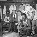 FILE - In this April 9, 1964, Boston Celtics, from left, Bill Russell, coach Red Auerbach, Tommy Heinsohn, Jim Locustoff, and K.C. Jones celebrate in the locker room after clinching their eighth straight Eastern Division playoff title at the Boston Garden in Boston. Tommy Heinsohn, who as a Boston Celtics player, coach and broadcaster was with the team for all 17 of its NBA championships, has died. He was 86. The team confirmed Heinsohn's death on Tuesday, Nov. 10, 2020. (AP Photo, File)