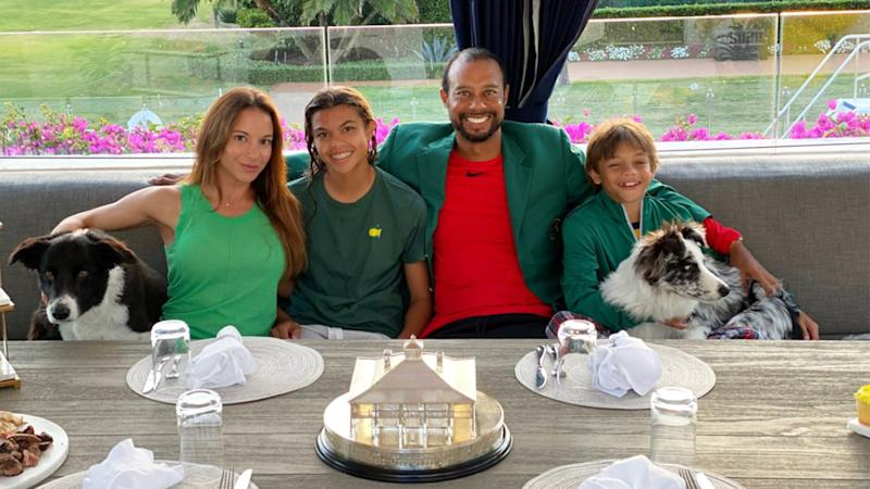 Tiger Woods smiling and hugging his family celebrating his Masters champions dinner at home.