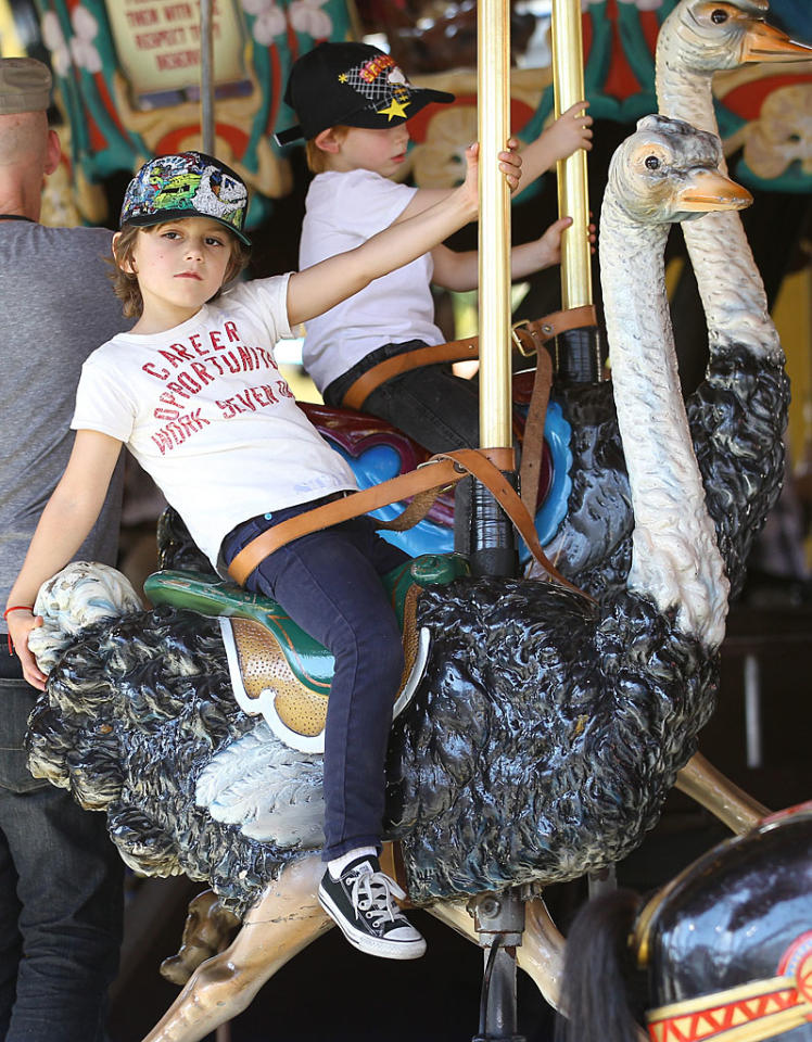 The always-stylish Kingston held on tight for a ride on a plastic ostrich on the merry-go-round at the theme park. (3/3/2012)
