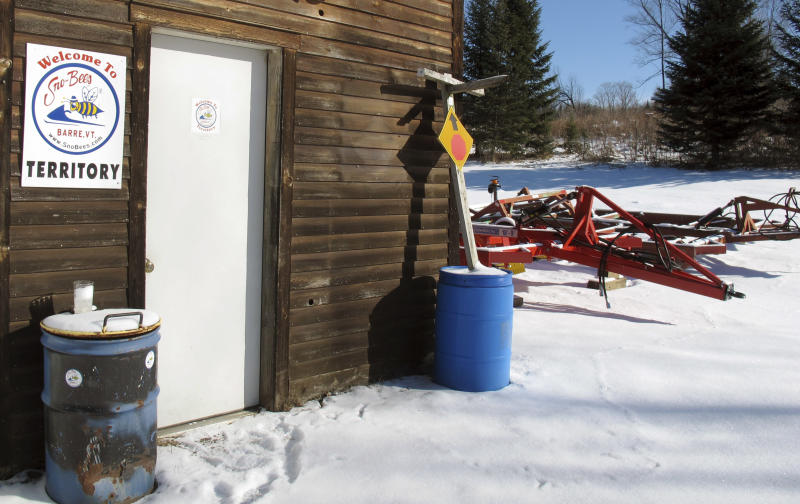 Snowmobile trail grooming equipment sits unused outside a garage belonging to the Barre Sno-Bees snowmobile Club Wednesday, Jan. 22, 2014, in Barre, Vt. Below-zero temperatures are being reported across Vermont but unlike most of New England and parts of the mid-Atlantic, heavy snow continues to evade the state. (AP Photo/Wilson Ring)