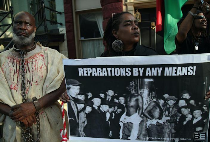 """<span class=""""caption"""">Activists mark National Reparations Day in Washington, D.C., on July 1, 2019.</span> <span class=""""attribution""""><a class=""""link rapid-noclick-resp"""" href=""""https://www.gettyimages.com/detail/news-photo/activists-stage-a-protest-to-mark-the-national-reparations-news-photo/1159502247?adppopup=true"""" rel=""""nofollow noopener"""" target=""""_blank"""" data-ylk=""""slk:Alex Wong/Getty Images"""">Alex Wong/Getty Images</a></span>"""