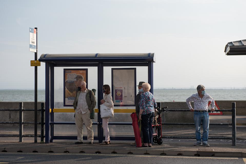 SOUTHEND-ON-SEA, ENGLAND - SEPTEMBER 20: A group of people wearing face masks wait for a bus at the bus stop on September 20, 2020 in Southend on Sea, London. (Photo by John Keeble/Getty Images)