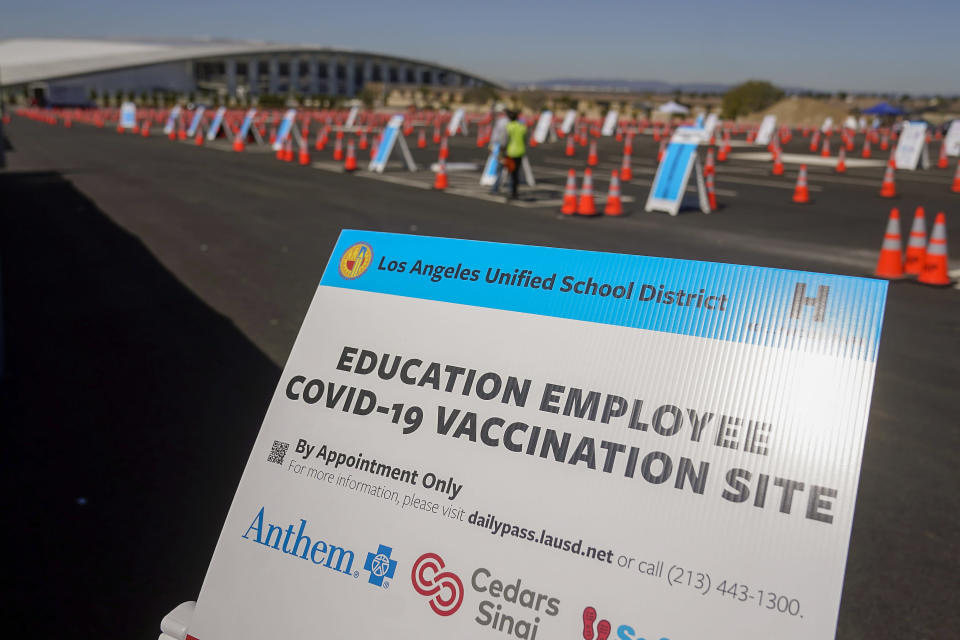 FILE - In this March 2, 2021, file photo, a sign is displayed at a COVID-19 vaccination site for employees of the Los Angeles School District, LAUSD, in the parking lot of SOFI Stadium in Inglewood, Calif. Public schools have struggled for years with teacher shortages, particularly in math, science, special education and languages. But the pandemic has exacerbated the problem. The stresses of teaching in the COVID-era caused a spike in teacher retirements and resignations. On top of that, schools now have to hire all kinds of additional staff, like tutors and special aides to help kids make up for learning losses, and more teachers to run online school for those not ready to return. (AP Photo/Marcio Jose Sanchez, File)
