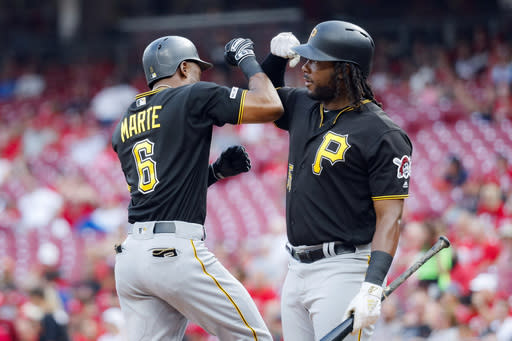 Pittsburgh Pirates' Starling Marte (6) celebrates with Josh Bell, right, after hitting a solo home run off Cincinnati Reds starting pitcher Sonny Gray in the first inning of a baseball game, Monday, July 29, 2019, in Cincinnati. (AP Photo/John Minchillo)