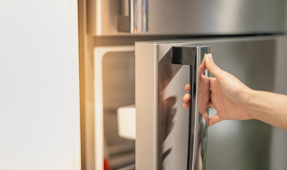 Female hand opening a refrigerator door for find the food and ingredient preparing to cooking in their home.