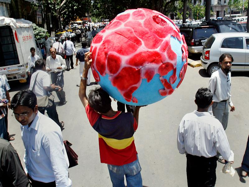 """An activist carries a globe with the land masses represented by """"meat"""" after a demonstration by animal rights group 'People for the Ethical Treatment of Animals' (PETA) in Mumbai. Reuters"""