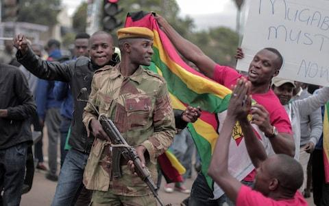 People cheer soldiers during a march in the streets to demand that President Robert Mugabe resign and step down from power in Harare, Zimbabwe, on November 19, 2017 - Credit: Barcroft Media