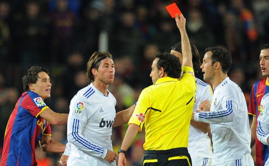 """The referee shows a red card to Real Madrid's defender Sergio Ramos (2ndL) during the Spanish league """"clasico"""" football match FC Barcelona vs Real Madrid on November 29, 2010 at Camp Nou stadium in Barcelona. Barcelona won 5-0. AFP PHOTO/ LLUIS GENE (Photo by LLUIS GENE / AFP)"""