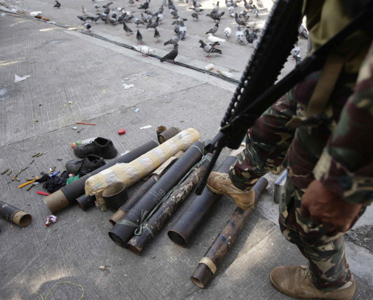 A Government trooper checks mortar casings recovered from the Muslim rebels, Sunday Sept. 15, 2013 in Zamboanga city, southern Philippines. The standoff, which began Monday when about 200 Moro National Liberation Front guerrillas stormed several coastal communities in Zamboanga city and seized several residents, has displaced more than 60,000, forced the closure of businesses and resulted in more than 50 deaths so far.(AP Photo/Bullit Marquez)