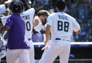 Colorado Rockies' Charlie Blackmon, center, is showered by teammates as Blackmon crosses home plate after hitting a solo home run off Los Angeles Dodgers relief pitcher Phil Bickford during the 10th inning of a baseball game Sunday, July 18, 2021, in Denver. The Rockies won 6-5. (AP Photo/David Zalubowski)
