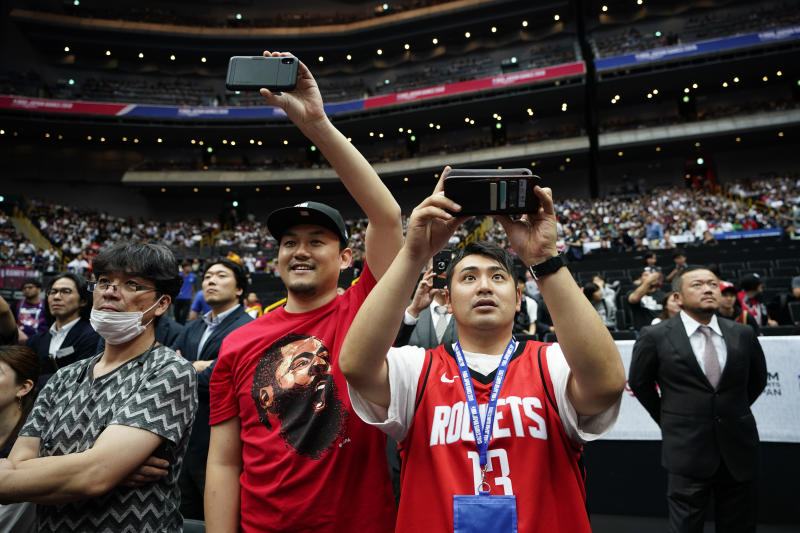 Fans take pictures as players warm up before an NBA preseason basketball game between the Houston Rockets and the Toronto Raptors Tuesday, Oct. 8, 2019, in Saitama, near Tokyo. (AP Photo/Jae C. Hong)