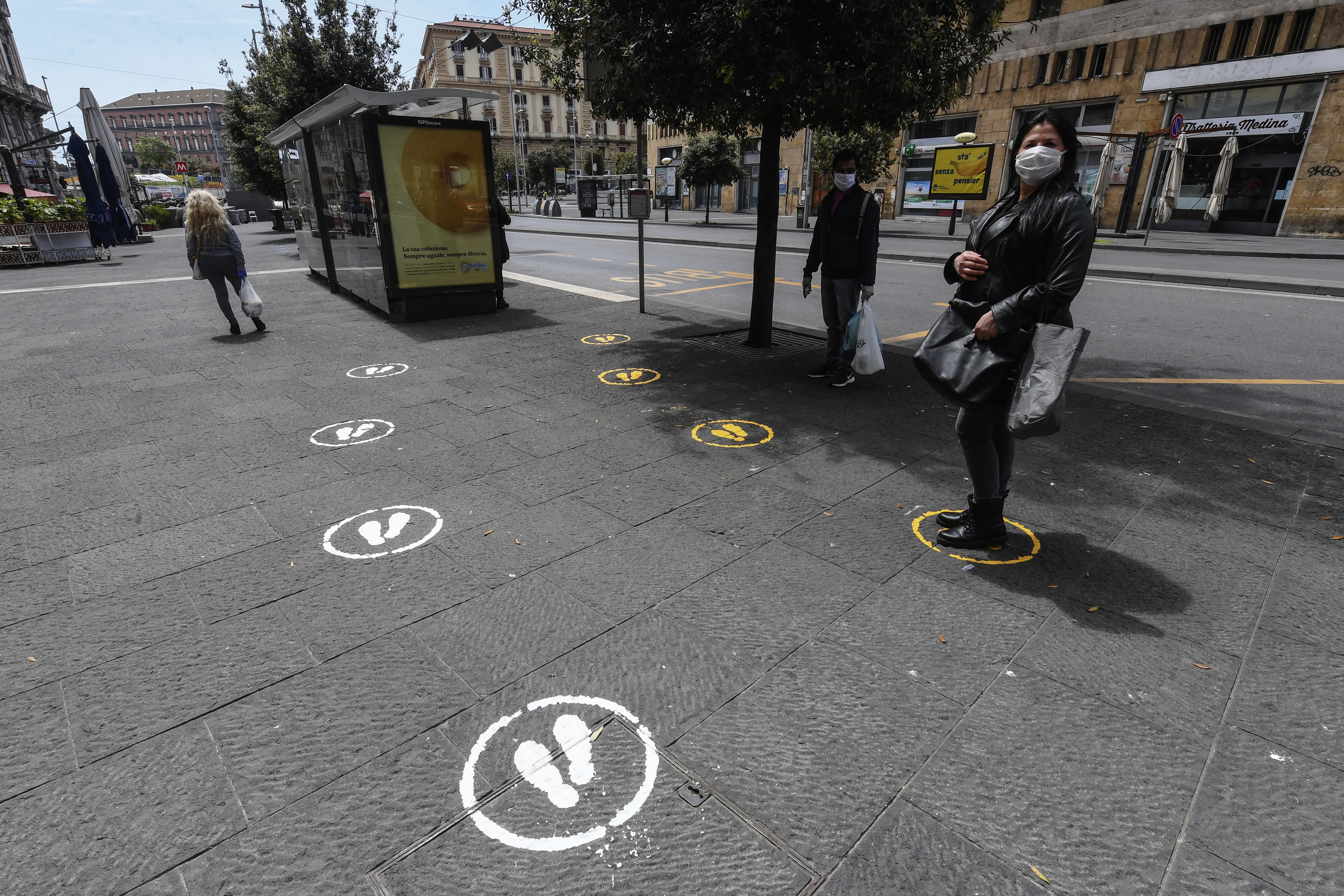 NAPLES, CAMPANIA, ITALY - 2020/05/05: A woman wearing protective mask is next to a bus stop with safe distance signs. Italy begins a staged end to a nationwide lockdown due to the spread of the coronavirus disease. (Photo by Salvatore Laporta/KONTROLAB/LightRocket via Getty Images)