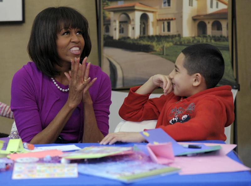 First lady Michelle Obama talks with Jorge Ortiz during her visit to the Fisher House, located at Walter Reed National Military Medical Center in Bethesda, Md., Wednesday, March 20, 2013, for a pre-Easter celebration with military families and children. (AP Photo/Susan Walsh)