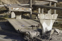 FILE - In this Jan. 17, 1994, file photo, the covered body of Los Angeles Police Officer Clarence Wayne Dean lies near his motorcycle which plunged off the State Highway 14 overpass that collapsed onto Interstate 5, after a magnitude-6.7 Northridge earthquake in Los Angeles. (AP Photo/Doug Pizac, File)