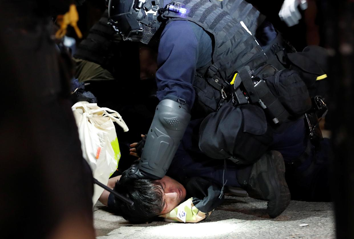An antigovernment protester is restrained by riot police in Hong Kong, Oct. 20, 2019. (Photo: Kim Kyung-Hoon/Reuters)