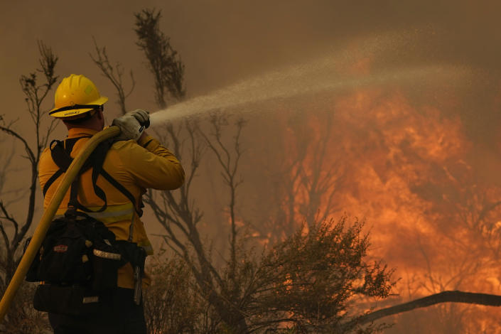 Jesse Vasquez, of the San Bernardino County Fire Department, hoses down hot spots from the Bobcat Fire on Saturday, Sept. 19, 2020, in Valyermo, Calif. (AP Photo/Marcio Jose Sanchez)