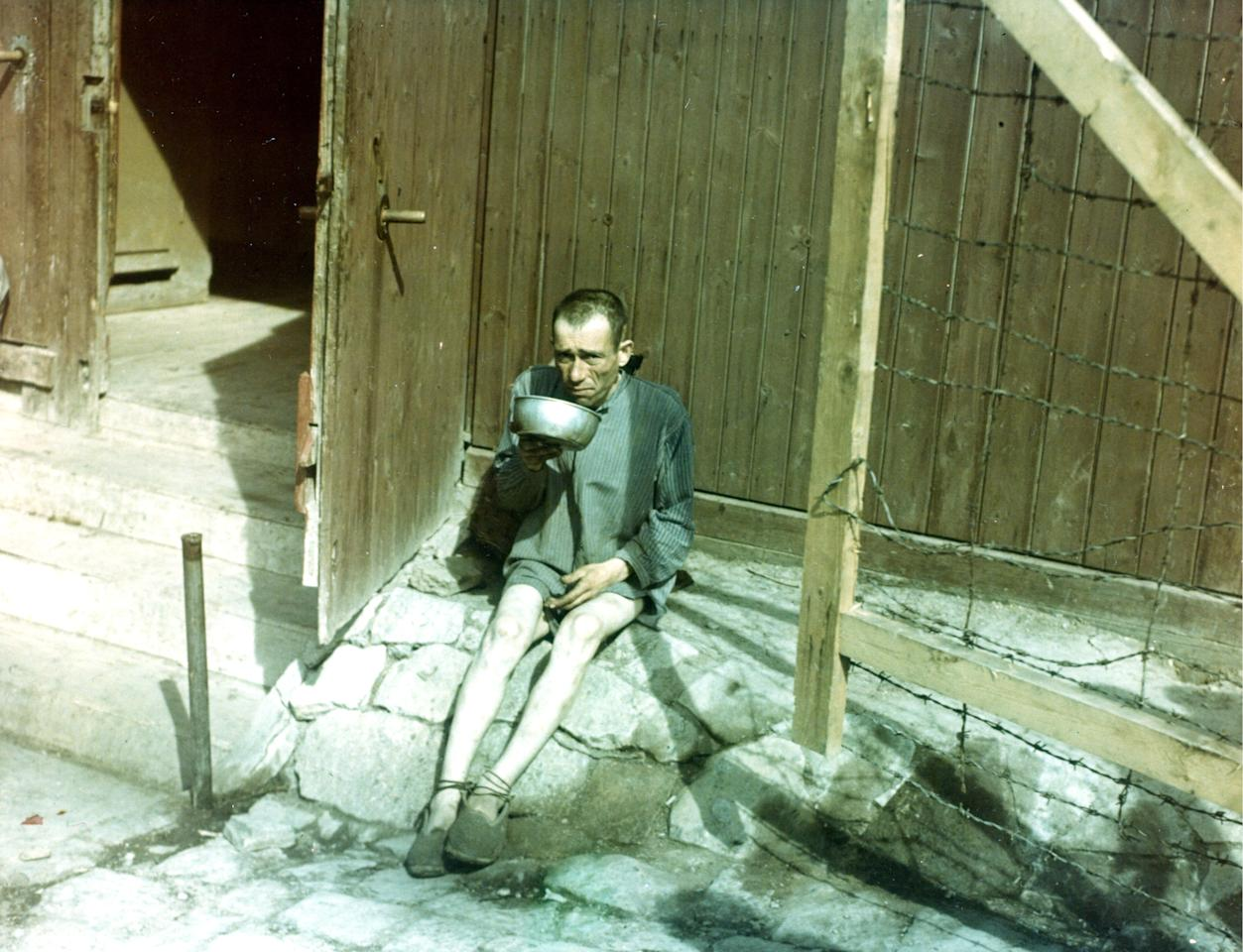 An emaciated former prisoner of the Buchenwald concentration camp drinks from a metal bowl shortly after the camp's liberation, Weimar, Germany, 1945. (Photo by PhotoQuest/Getty Images)