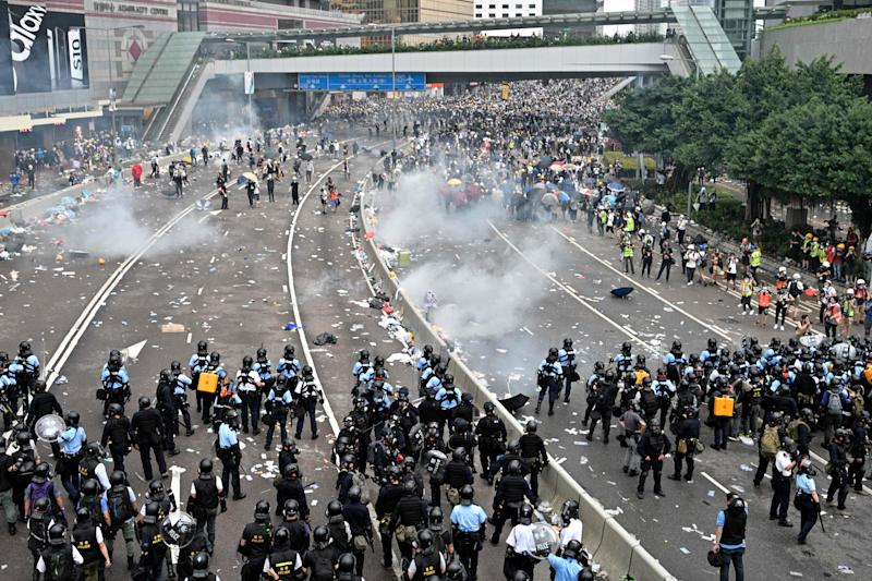 Protesters retreat after police fired tear gas during a rally against a controversial extradition law proposal in Hong Kong on June 12, 2019.