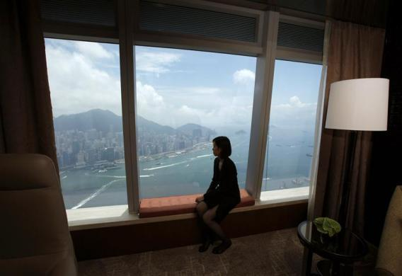 An employee poses in front of a window overlooking Victoria Harbour from a standard room on the 109th floor of the Ritz-Carlton Hotel in the International Commerce Centre (ICC), the world's fourth tallest building, in Hong Kong May 11, 2011.