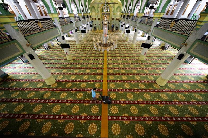 A worker cleaning the carpets at Sultan Mosque. (PHOTO: Muis)