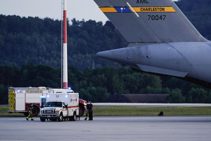 An ambulance stands next to a transport plane carrying people flown out of Afghanistan at Ramstein Air Base, in Ramstein-Miesenbach, Germany, Friday, Aug. 2021. (Uwe Anspach/dpa via AP)