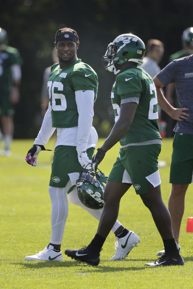New York Jets' Le'Veon Bell, left, talks with Elijah McGuire during a practice at the NFL football team's training camp in Florham Park, N.J., Friday, July 26, 2019. (AP Photo/Seth Wenig)