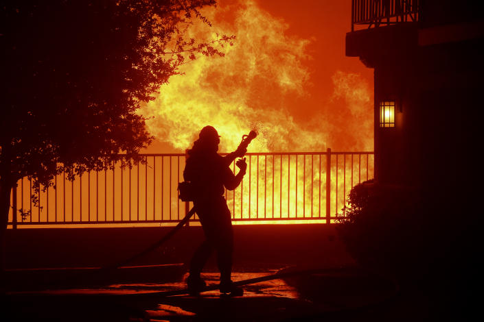 In this Thursday, Oct. 10, 2019 photo, a firefighter waits for water as the Saddleridge fire flares up near homes in Sylmar, Calif. (Photo: Michael Owen Baker/AP)