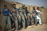 Afghan policemen simulate weapons orientation during a training session with U.S. soldiers from 2nd PLT Diablos 552nd Military Police Company, on the outskirts of Kandahar City, Afghanistan, Tuesday, Oct. 26, 2010. (AP Photo/Rodrigo Abd)